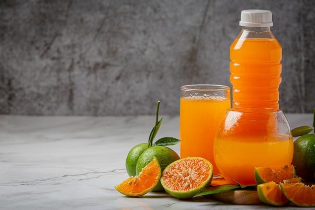 Un bicchiere di succo d'arancia e frutta fresca sul pavimento con cubetti di ghiaccio.