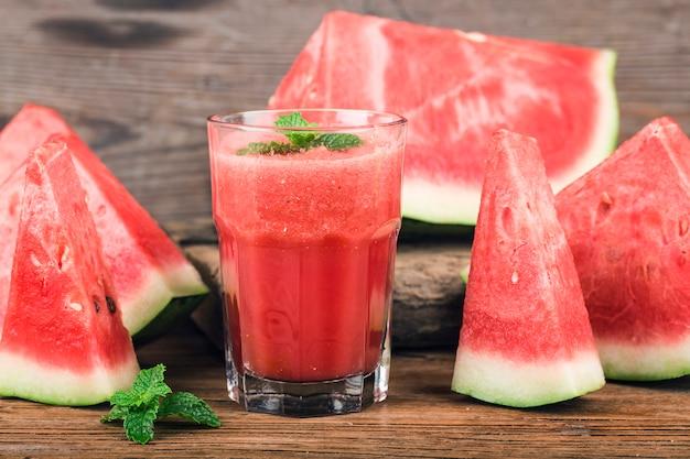 Un bicchiere di succo di anguria fresca su uno sfondo di tavola di legno