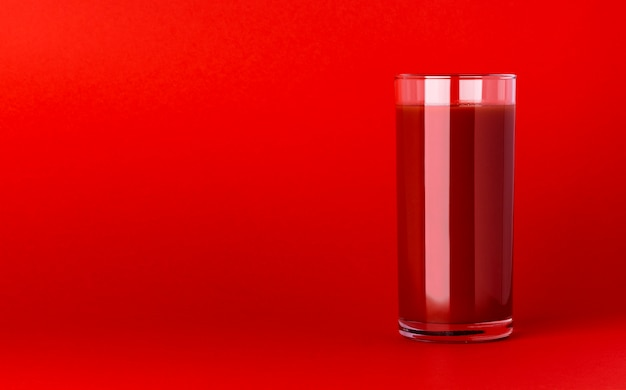 Un bicchiere di succo di pomodoro su sfondo rosso con copia spazio, sanguinosa mary cocktail