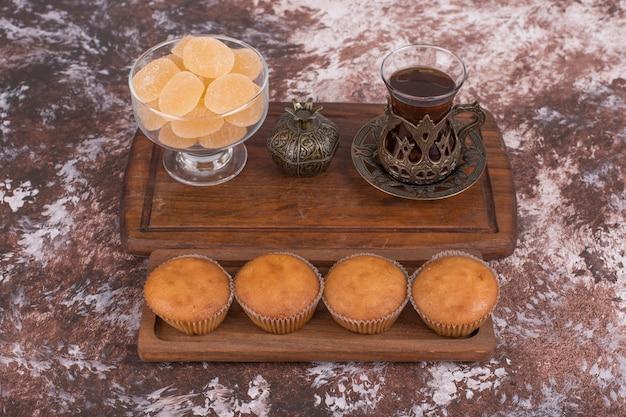 Un bicchiere di tè in piatti etnici con marmellate e cupcakes su un piatto di legno