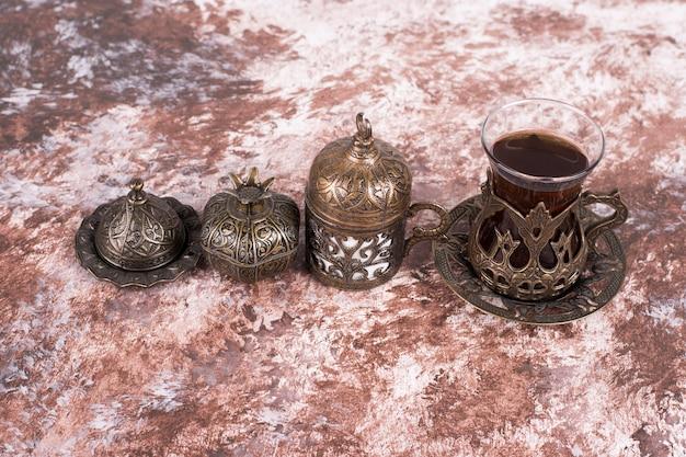 Un bicchiere di tè in piatti etnici sul tavolo di marmo