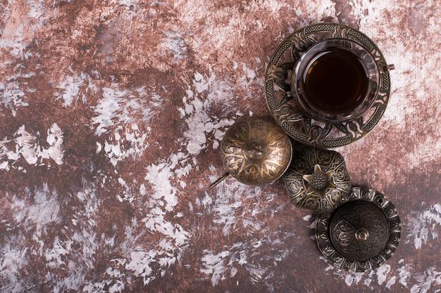 Un bicchiere di tè o caffè espresso in piatti etnici