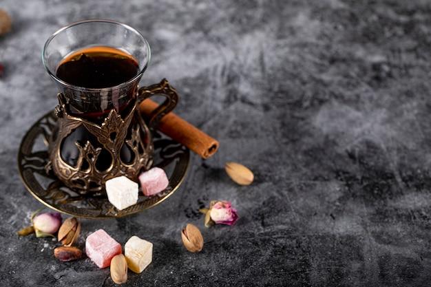 Un bicchiere di tè, pistacchi, lokum turco e cannella su un marmo blu