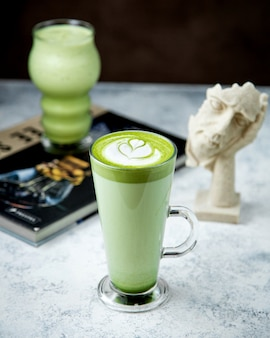 Un bicchiere di tè verde matcha con latte art in cima 1