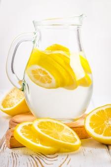 Un bicchiere di vetro e una brocca di limonata fredda su uno sfondo di legno bianco circondato da limoni.