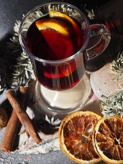 Un bicchiere di vin brulé su uno sfondo scuro con coni, spezie, il concetto del nuovo anno, in polvere con la neve