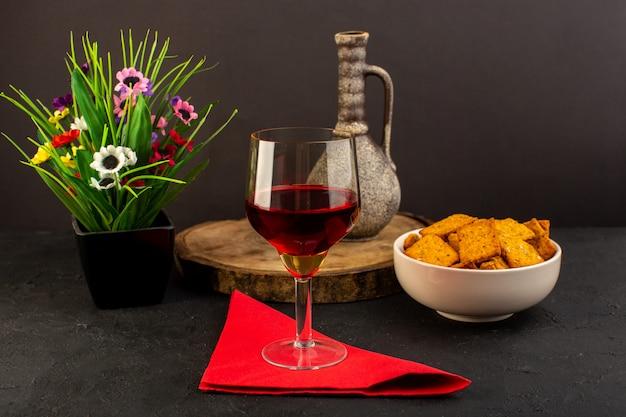 Un bicchiere di vino con vista frontale insieme a fiori e patatine all'interno del piatto sulla scrivania scura