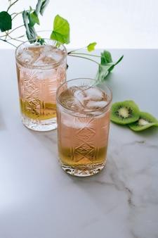 Un bicchiere di vino rosa in un bicchiere di cristallo su marmo, edera verde e sole splendente