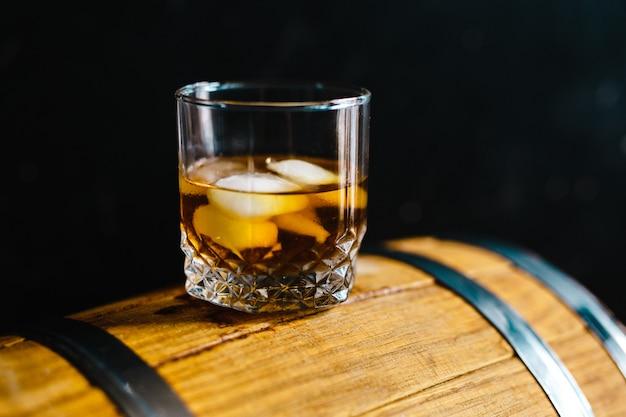 Un bicchiere di whisky seduto su una botte di legno