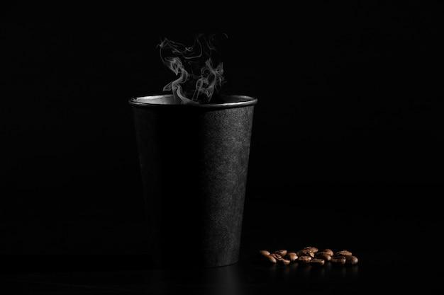 Un bicchiere nero di caffè caldo con chicchi di caffè sparsi su uno sfondo nero. avvicinamento