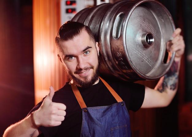 Un birraio con la barba in grembiule tiene un barile di metallo con la birra in mano e sorride