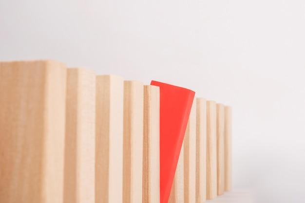 Un blocco di legno rosso è eccezionale e spicca tra la folla. sii un concetto diverso.