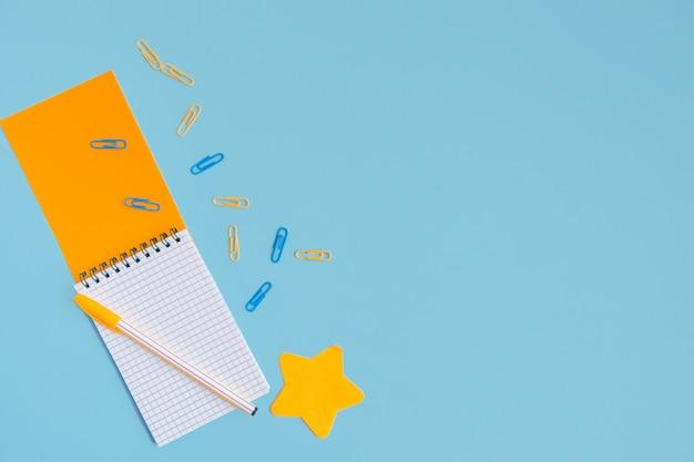 Un blocco note arancione aperto con una penna, un adesivo a forma di stella e graffette sparse