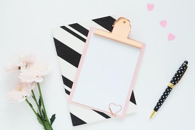 Un blocco per appunti rosa, un quaderno a strisce bianco e nero, tre fiori di crisantemo rosa, una penna a pois nera e cuori di plastica.