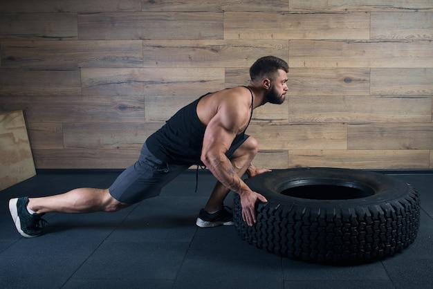 Un bodybuilder con un tatuaggio e la barba sta spingendo una gomma in una palestra