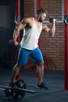 Un bodybuilder tagliuzzato sta facendo riccioli bicipiti con manubri