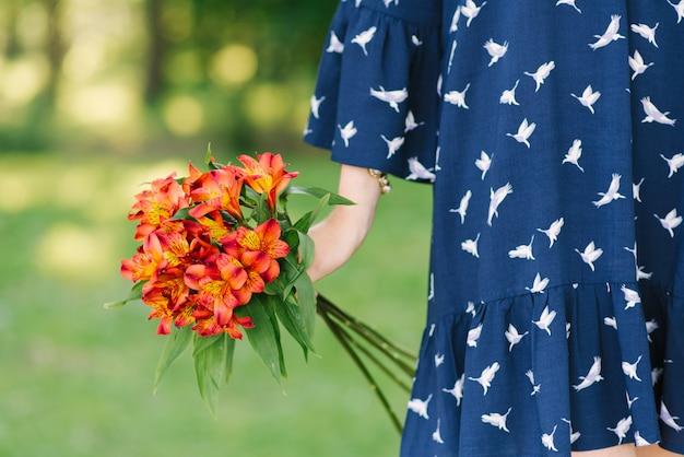Un bouquet di arancia alstroemeria nelle mani di una ragazza. avvicinamento