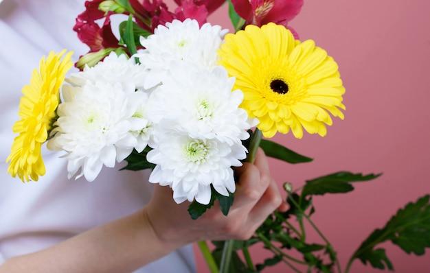 Un bouquet di bellissimi fiori nelle mani di una ragazza