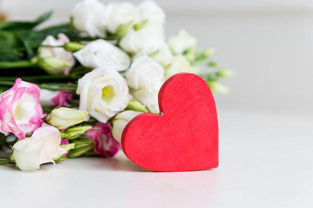 Un bouquet di fiori eustoma bianchi con un cuore su bianco