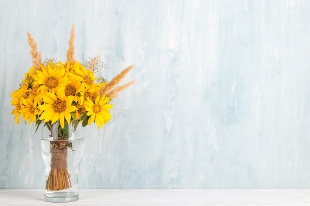 Un bouquet di fiori gialli, girasoli, in un vaso di vetro sull'azzurro. copia spazio.