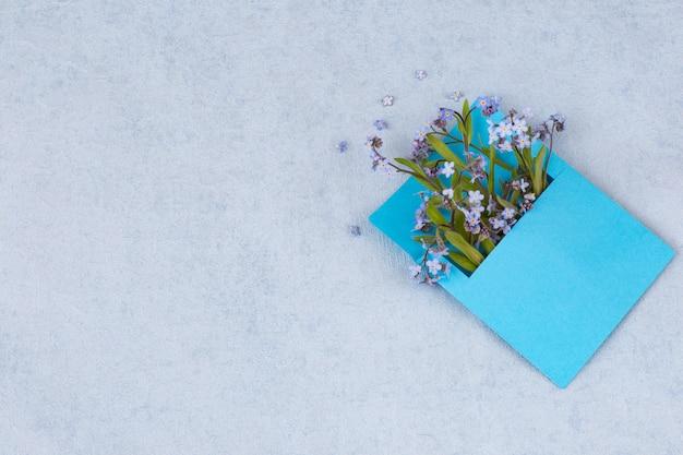 Un bouquet di forget me nots in una busta blu e spazio libero per il testo