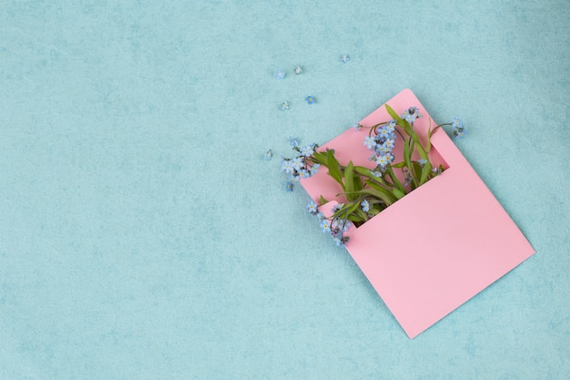 Un bouquet di forget me nots in una busta rosa e spazio libero per il testo