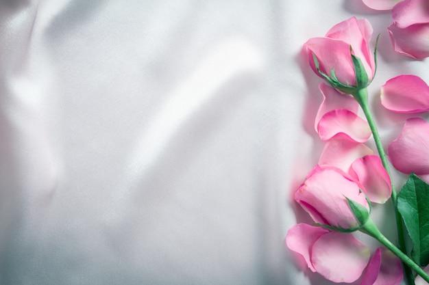 Un bouquet di petali di rose rosa dolce su morbido tessuto di seta rosa, carta di romanticismo e amore