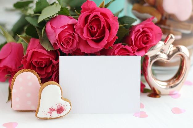 Un bouquet di rose rosa brillante, due cuori di pan di zenzero, una figurina di mela dorata e una foglia bianca - uno spazio vuoto per il testo. biglietto d'auguri.