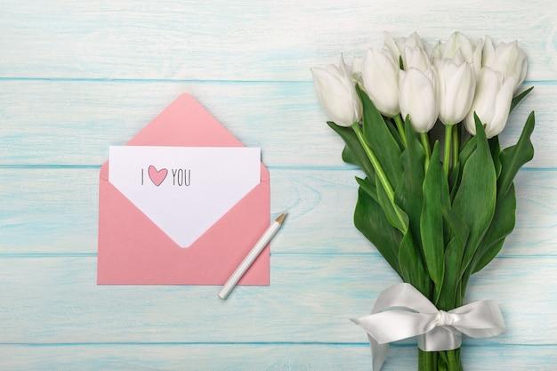Un bouquet di tulipani bianchi con nota d'amore e busta di colore su tavole di legno blu