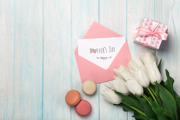 Un bouquet di tulipani bianchi con una confezione regalo, macarons, note d'amore e busta colorata su assi di legno blu. festa della mamma