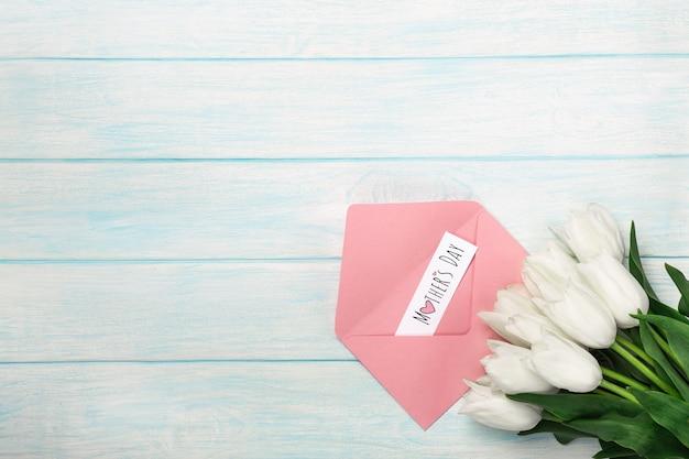 Un bouquet di tulipani bianchi con una nota di amore e busta di colore su tavole di legno blu. festa della mamma