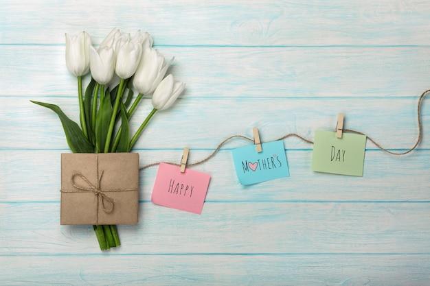 Un bouquet di tulipani bianchi e busta con adesivi a colori con mollette su una corda e tavole di legno blu. festa della mamma