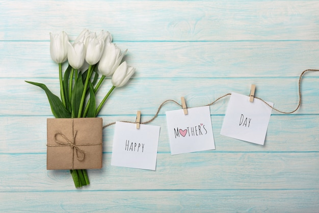Un bouquet di tulipani bianchi e busta con adesivi con mollette su una corda e tavole di legno blu. festa della mamma