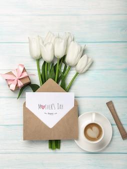 Un bouquet di tulipani bianchi, tazza di caffè, confezione regalo con una nota d'amore e busta su tavole di legno blu. festa della mamma