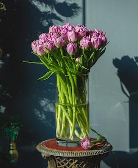 Un bouquet di tulipani rosa con foglie verdi all'interno di un vaso
