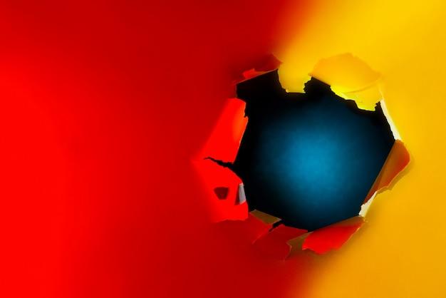 Un buco sfilacciato sullo sfondo di carta brillante illuminato da neon