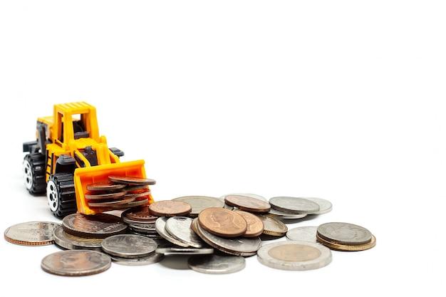 Un bulldozer giallo del giocattolo con la pila di monete su bianco