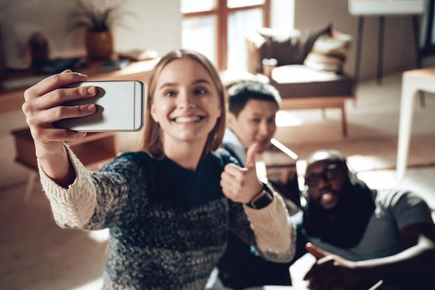 Un buon lavoro i ragazzi multirazziali prendono selfie in ufficio.