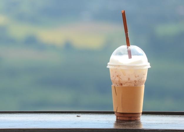 Un caffè ghiacciato in tazza di plastica con vista natuale come sfondo.