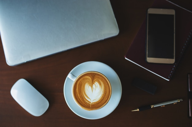 Un caffè latte e un computer portatile sul tavolo.