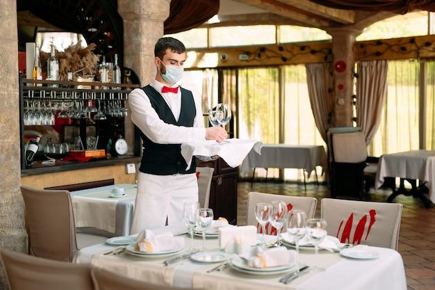 Un cameriere con una mascherina protettiva serve il tavolo del ristorante.