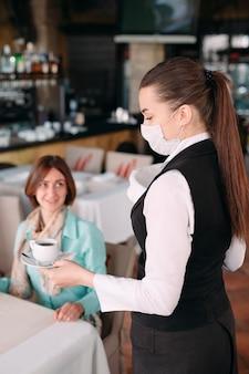 Un cameriere dall'aspetto europeo con una maschera medica serve il caffè.