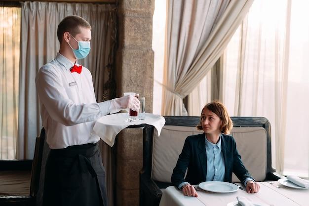 Un cameriere dall'aspetto europeo con una mascherina medica serve caffè latte.