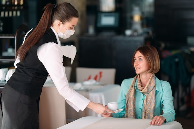 Un cameriere dall'aspetto europeo con una mascherina medica serve caffè.