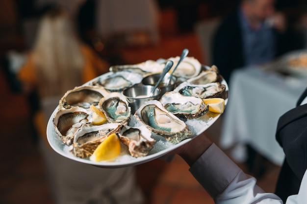 Un cameriere tiene una porzione di ostriche in un ristorante