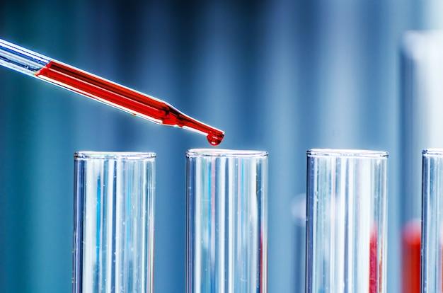 Un campione cadente della pipetta in una provetta, fondo di scienza astratta