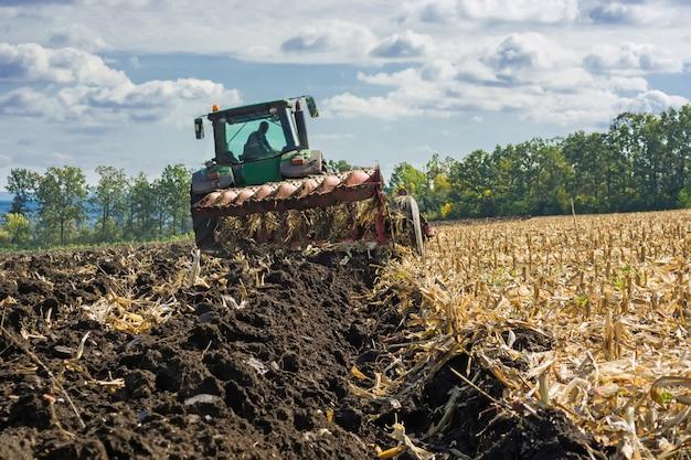 Un campo arato dopo la raccolta del mais con un trattore completo di aratro a otto corpi