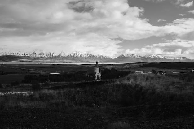 Un campo con una chiesa in lontananza con un bel cielo nuvoloso