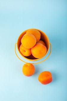 Un canestro di vista superiore con la frutta pastosa fresca dolce delle albicocche dentro il canestro giallo isolato