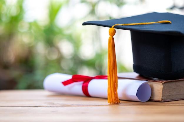 Un cappello di laurea nero e un certificato collocato su un vecchio libro